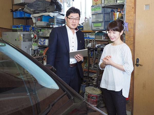 写真:車を査定する男性と車の所有者の女性