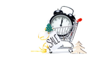 Picture of trolley with gold alarm clock, Christmas tree, greeting card, ribbon on blank white background. Place for text