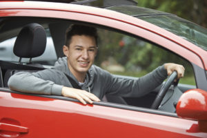 Newly Qualified Teenage Boy Driver Sitting In Car