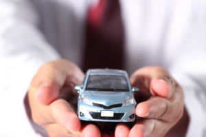 The blue car is in businessman hand
